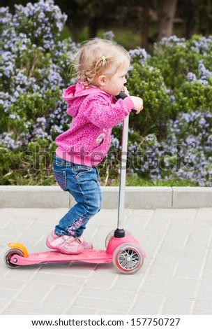 toddler girl on a scooter in a park in spring day - stock photo