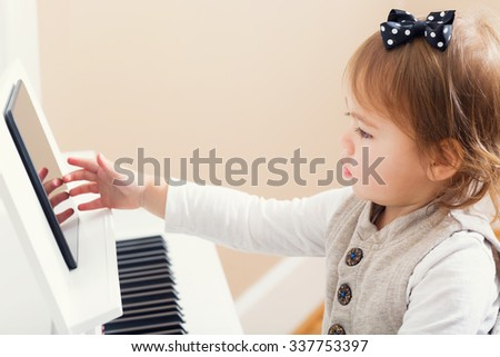 Toddler girl playing the piano while reading sheet music from her tablet - stock photo