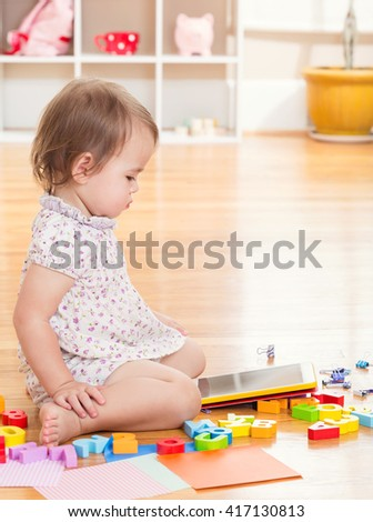 Toddler girl playing with her tablet computer in her house - stock photo
