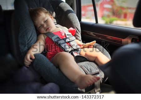 Toddler girl sleeping in child car seat. - stock photo