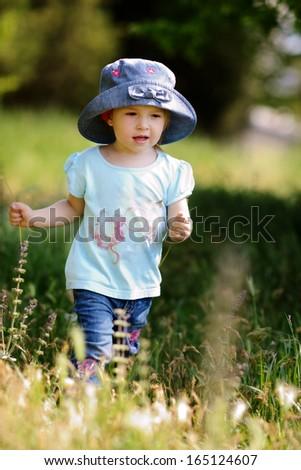 toddler girl walking in green grass - stock photo
