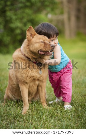Toddler giving hug to dog. - stock photo