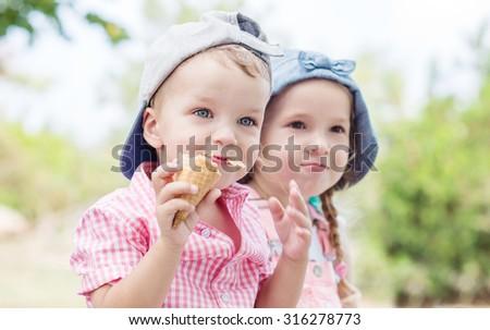 Toddler happy children eating ice cream in summer - stock photo