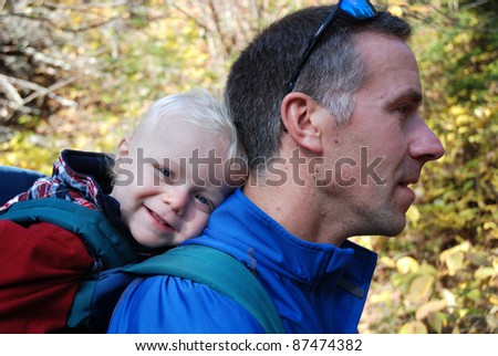 toddler in pack on dad's back - stock photo