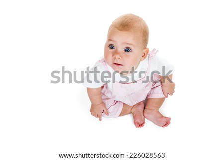 Toddler in pink jumpsuit sitting and looking up isolated on white background top view - stock photo