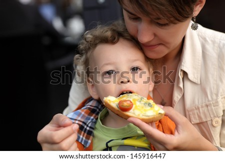 Toddler is eating bruschetta in a restaurant - stock photo
