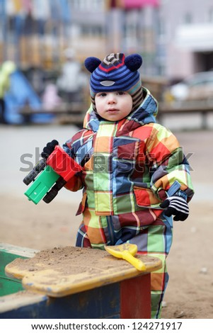 Toddler is with toy car near sandbox at playground - stock photo