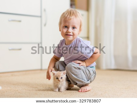 Toddler kid boy plays with kitten in children room - stock photo