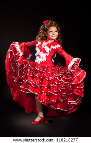 toddler little girl dancing flamenco in traditional spanish red dress. Adorable child from Andalusia with curly hair dancing Gypsy dance. Portrait of artist baby in carnival bellydancing costume. - stock photo