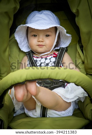 Toddler mixed race sitting in green stroller in summertime - stock photo