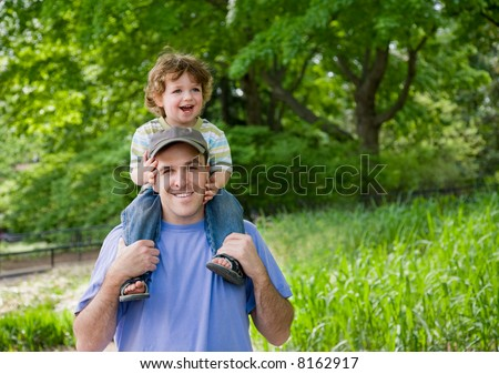 Toddler on dad's shoulders - stock photo