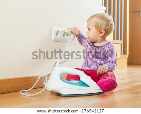 Toddler playing with electric iron on floor at home - stock photo