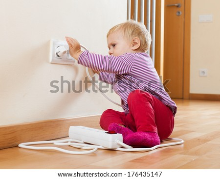 Toddler playing with electrical extension on floor at home - stock photo