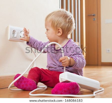 Toddler playing with electricity at home - stock photo