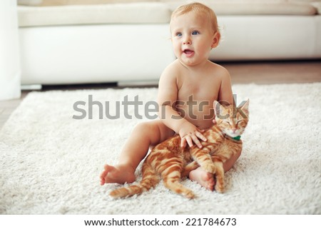 Toddler playing with red cat on a white carpet at home - stock photo