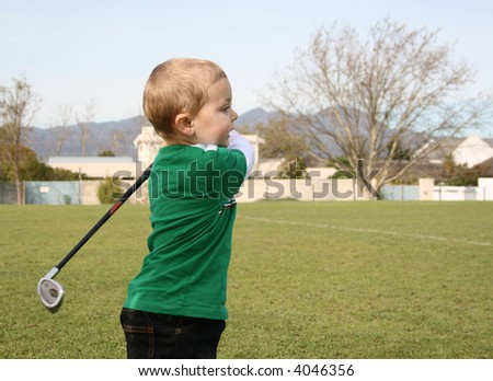 Toddler practising golf on the driving range - stock photo