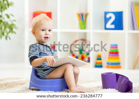 toddler sitting on chamber pot playing tablet pc with toilet paper rolls - stock photo