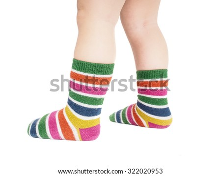Toddler standing in striped socks and bare legs isolated on white - stock photo