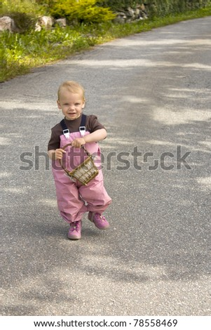 Toddler walking down a road, holding a basket - stock photo