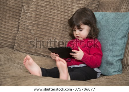 Toddler watching screen on tablet - stock photo