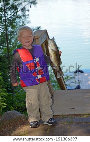 toddler with a large mouth bass - stock photo