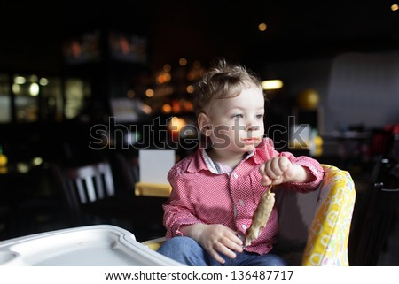 Toddler with kebab in a high chair at a restaurant - stock photo