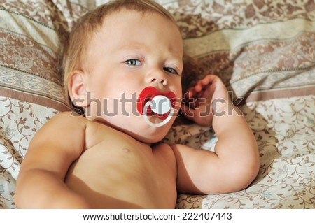 toddler with pacifier lying on bed - stock photo