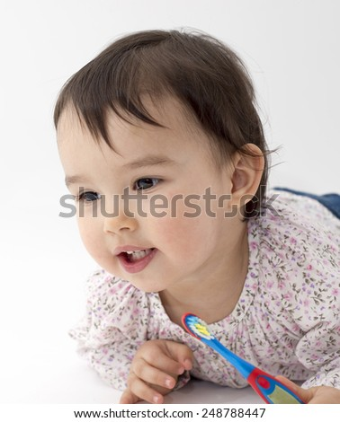Toddler with toothbrush in her hand - stock photo
