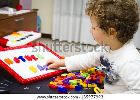 Toddler (2/3 years old) writes Mother's Day with toy letters - stock photo
