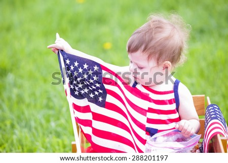 Toddlers having fun in the park for July Fourth. - stock photo
