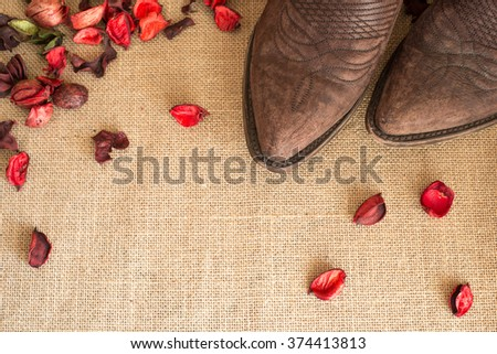 toes of cowboy boots on country fabric with dried red flowers all around - negative space on bottom left - stock photo
