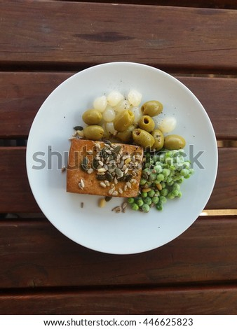 Tofu based dish with green olives, pickled onions and frozen peas - stock photo