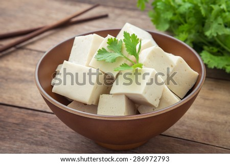 Tofu cubes in bowl and parsley  - stock photo