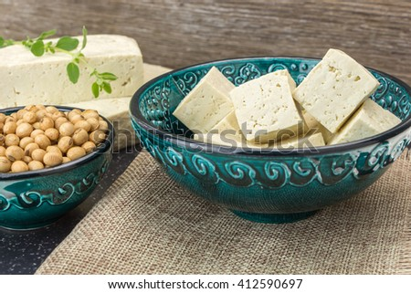 Tofu cut into cubes and soybeans in bowls, on wooden background. - stock photo