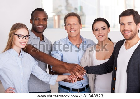 Together we are stronger! Group of cheerful business people in casual wear standing close to each other and holding hands together - stock photo