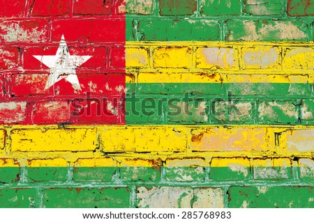 Togo flag painted on old brick wall texture background - stock photo