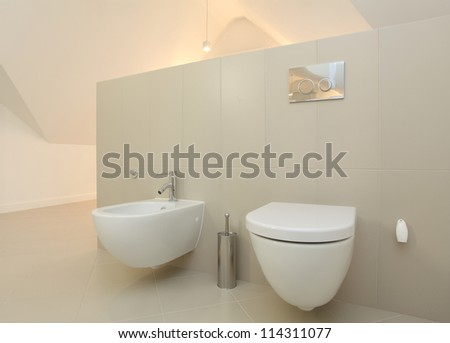 Toilet and bidet in bright modern bathroom - stock photo