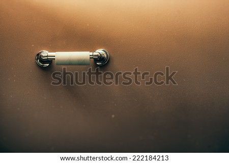 Toilet Paper Out. Empty toilet paper roll on wall of rustic looking bathroom. - stock photo