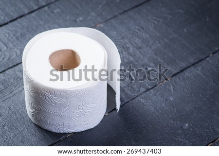 Toilet paper roll on the black wooden table - stock photo
