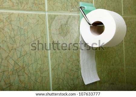 Toilet roll in green toilet, lavatory convenience restroom full tiled wall - stock photo