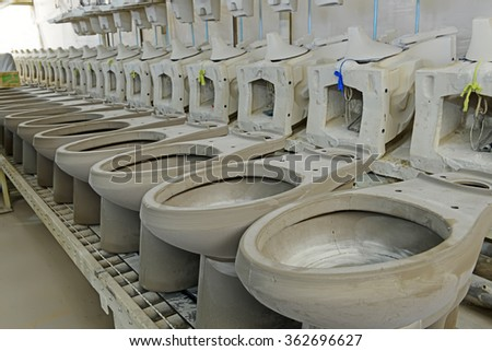 toilet unpainted clay idol in production workshop, closeup of photo - stock photo