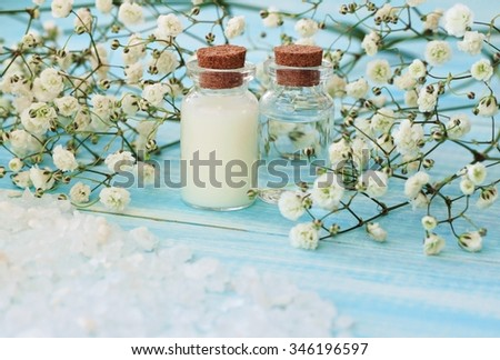 Toiletries tonic and ethereal oil on light blur wooden background, sea salt, framed decorative flowers. Sea salt mineral beauty care. - stock photo