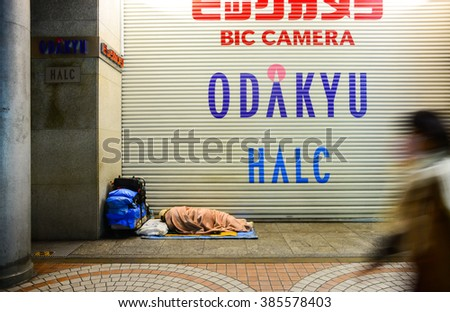 Tokyo - Dec 3, 2015 - An unidentified homeless man sleep overnight on the pavement at Shinjuku area - stock photo