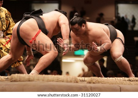 TOKYO - JANUARY 21: Close-up of two sumo wrestlers ready to engage in the Tokyo Grand Sumo Tournament January 21, 2009 in Tokyo, Japan. - stock photo