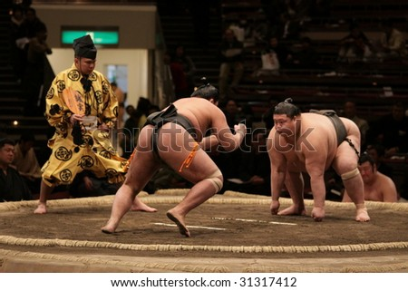 TOKYO - JANUARY 21: Sumo wrestler charging in on waiting opponent in the Tokyo Grand Sumo Tournament January 21, 2009 in Tokyo, Japan. - stock photo