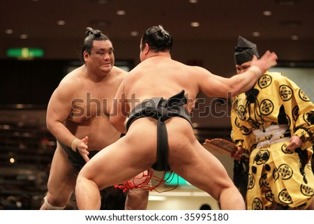 TOKYO - JANUARY 21: Sumo wrestlers engaged in a fight in the Tokyo Grand Sumo Tournament January 21, 2009 in Tokyo, Japan. - stock photo