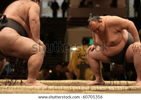 TOKYO - JANUARY 18: Two sumo wrestlers focusing and getting ready for a fight in the Tokyo Grand Sumo Tournament January 18, 2010 in Tokyo, Japan. - stock photo