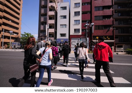 Tokyo, Japan - April 23, 2014 : Tourists and business people crossing the street at tokyo, Japan - stock photo