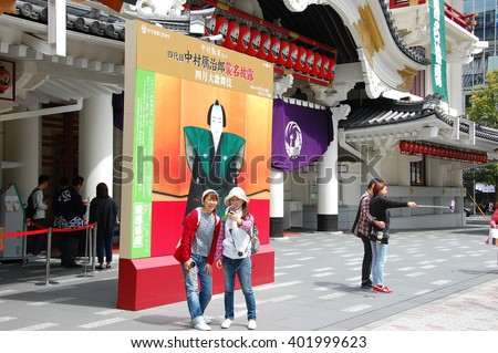 TOKYO JAPAN - April 18, 2015: Tourists taking selfies in front of the Kabukiza theater in Ginza. It's the most famous kabuki theater in Japan. Opened in 1889 and the recent reconstruction was in 2013. - stock photo