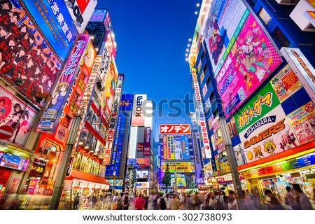 TOKYO, JAPAN - AUGUST 1, 2015: Crowds pass below colorful signs in Akihabara. The historic electronics district has evolved into a shopping area for video games, anime, manga, and computer goods. - stock photo